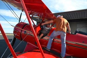 getting pushed into the Austin Biplane passenger seat