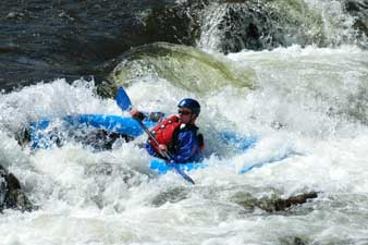 Kayaking down a rapid on the Roaring Fork